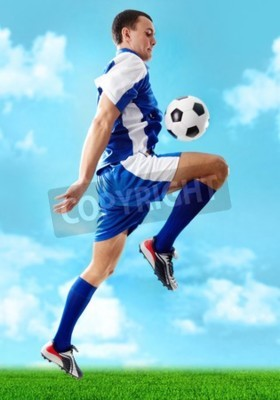 Portret piłkarz skoki z piłką na niebieskim tle