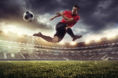 Naklejka Professional male football, soccer player on stadium background. Caucasian fit athlete practicing, playing excited in flight