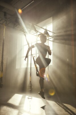 Naklejka Professional training. Full-length of young athletic woman in sports clothing training legs with trx fitness straps in the gym.