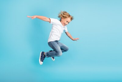 Naklejka Profile photo of young boy jump fly movement hands wear white shirt jeans sneakers isolated blue color background