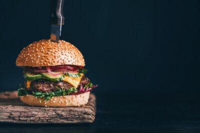 Naklejka Przepyszne, pyszne homemade hamburgery używane do siekania wołowiny. Na drewnianym stole. Hamburgery są wprowadzane noże.