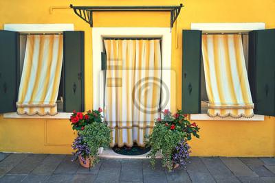 Przód żółty dom z kwiatu garnkiem w przodzie na wyspie Burano. Wenecja, Włochy. Toned