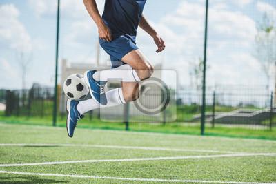 Przycięte strzału piłkarz skoków z piłką na boisko do piłki nożnej