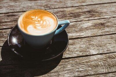Naklejka Puchar cappuccino ze sztuką kawy na drewnianym stole