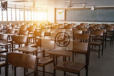 Naklejka Pusta sala lekcyjna z rocznika brzmienia drewnianymi krzesłami. Powrót do koncepcji szkoły.