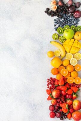 Naklejka Rainbow fruits berries background on white. Top view of strawberries blueberries cherries mango apple lemons oranges red currants plums blackberries, selective focus