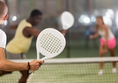 Naklejka Rear view of man with white racket playing padel tennis with friends at court