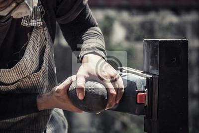 ręce trzyma maszynę szlifierki, polerki czarnej powierzchni drewna, nasycony odcień koloru