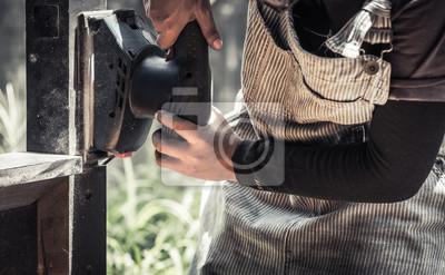 ręce w rękawiczkach trzymając maszynę szlifierki, polerki czarnej powierzchni drewna, nasycony odcień koloru