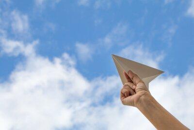 ręka trzyma papierowy samolot na tle nieba