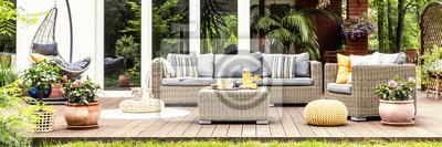 Naklejka Relaksujące miejsce na ciepły, letni dzień - stylowy drewniany taras z wiklinowymi meblami ogrodowymi, poduszkami, roślinami i kwiatami