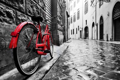 Naklejka Retro czerwony rower na brukowanej uliczce na starym mieście. Kolor w czerni i bieli