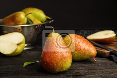 Naklejka Ripe juicy pears on dark wooden table against black background