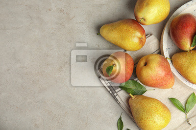Naklejka Ripe juicy pears on grey stone table, flat lay. Space for text