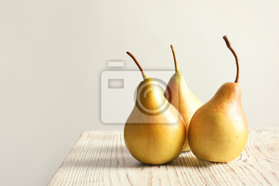 Naklejka Ripe pears on wooden table against light background. Space for text