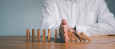 Naklejka Risk and Strategy in Business, Hand stopping wooden block domino business crisis effect or risk protection concept, prevention and development to stability