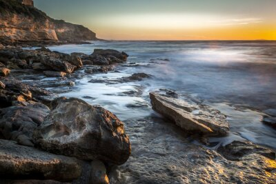 Rocky shore under a clear sky at sunset