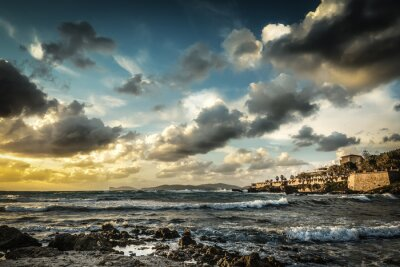 Rocky shore under a dramatic sky at sunset in Alghero