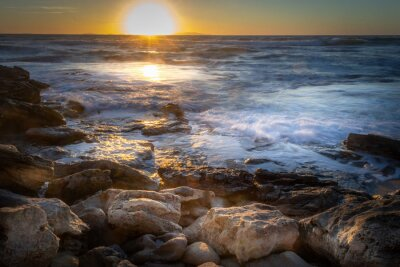 Rocky shore under a shining sun at sunset