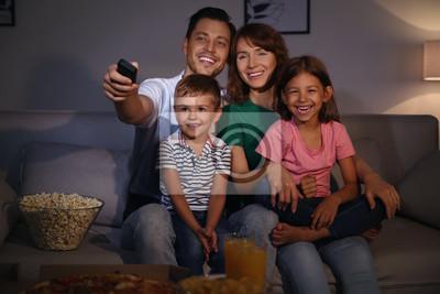 Rodzina ogląda telewizję w pokoju wieczorem