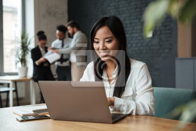 Naklejka Rozochocona młoda azjatykcia biznesowa kobieta używa laptop