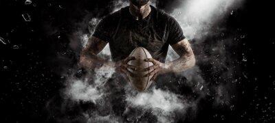 Naklejka Rugby player in action on dark