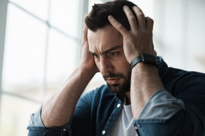 Naklejka Sad and worried man sit at home couch feeling negative emotions, depression and problems