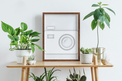 Naklejka Scandinavian room interior with mock up photo frame on the brown bamboo shelf with beautiful plants in differents hipster and design pots. White walls. Modern and floral concept of shelfs.
