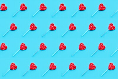 Seamless pattern. Valentines Day bckground. Lollipop candy hearts on blue background. Top view.