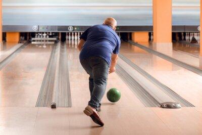 Naklejka Senior man playing bowling in club