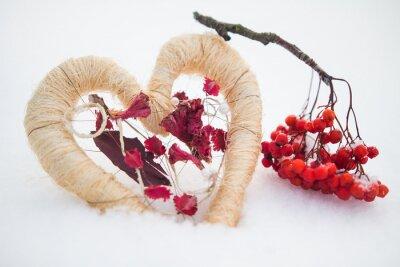 Serce z czerwonych owoców jagodowych na śniegu