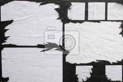 Naklejka Several sheets of white paper pasted on a black wall.