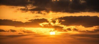 Shining sun and dark clouds at sunset