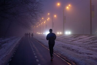 silhouette of a man jogging on the road in fog in the late winter evening in Kharkiv, Ukraine