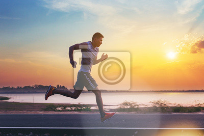 Naklejka Silhouette of man running sprinting on road. Fit male fitness runner during outdoor workout with sunset background