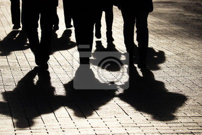 Naklejka Silhouettes and shadows of people on the city street. Crowd walking down on sidewalk, concept of strangers, crime, society, gang or population