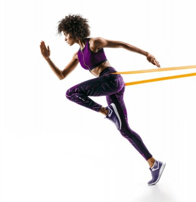 Naklejka Silna dziewczyna w sylwetce za pomocą zespołu oporu. Fotografia młoda afrykańska dziewczyna wykonuje sprawności fizycznych ćwiczenia odizolowywających na białym tle. Widok z boku