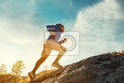 Naklejka Skyrunner skyrunning crosscountry concept with young athlete on big rock