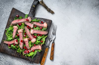 Naklejka Sliced grilled beef steak with arugula leaves salad on rustic  cutting board. White background. Top view. Copy space