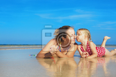 Śliczne dziewczyny całując Happy uśmiechnięta matka na morzu plaży