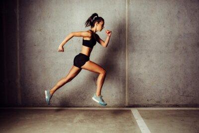 Naklejka Slim atrakcyjna sportsmenka uruchomiony przed betonowym murem