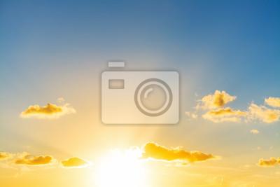 Słońca jaśnienie w niebieskim niebie przy zmierzchem