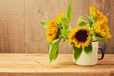 Naklejka Słoneczniki w zabytkowe kubek na drewnianym stole. Jesień w tle