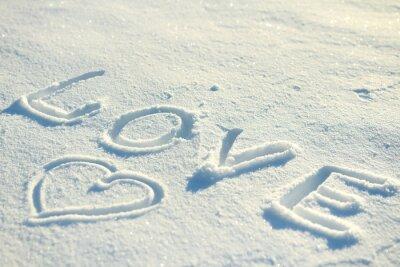 Słowo miłość i serce narysowane w śniegu.