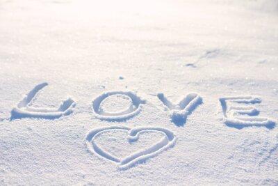Słowo miłość napisane na śniegu i serca