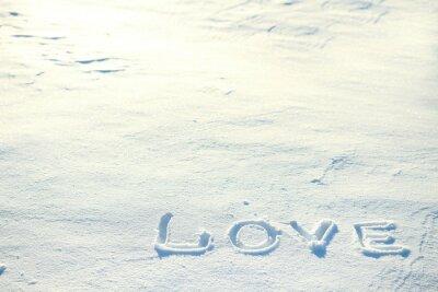 Słowo miłość narysowane w śniegu.