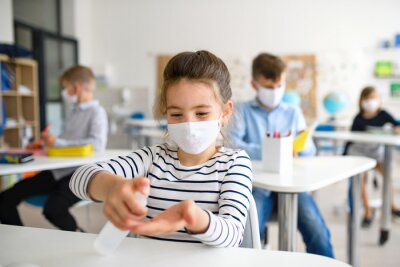 Small girl with face mask at school after covid-19 lockdown, disinfecting hands.
