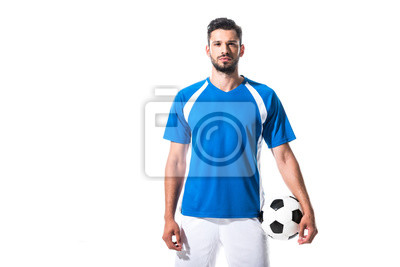 Naklejka soccer player holding ball and looking at camera Isolated On White