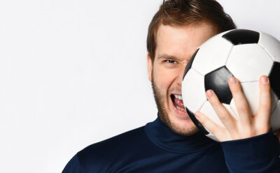 Soccer player in blue tracksuit has opened his mouth and covered half of his face with a ball, posing isolated on white. Close up