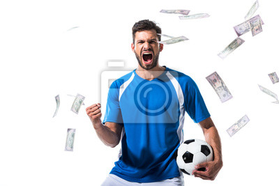 Naklejka soccer player with ball cheering with clenched hand near falling money Isolated On White